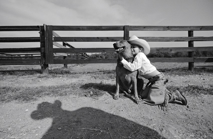 Four-year-old cowgirl Jess Abney and her dog in her father\'s shadow